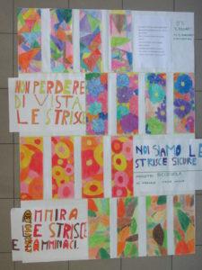 Cartellone con strisce pedonali bianche alternate ad altre con fiori colorati