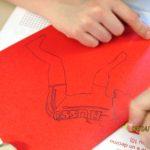 bambino che disegna la sagoma di un ciclista rosso