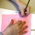 bambino che disegna la sagoma di un ciclista su cartoncino rosa