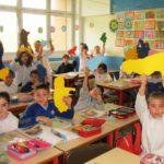 alunni della classe terza b seduti al proprio posto in aula cche alzano la mano facendo vedere una regione dell'italia colorata