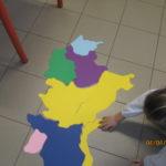 i bambini cominciano a comporre il puzzle di regioni colorate sul pavimento dell'aula